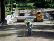 Paul Matos of J. Iapaluccio Inc. works at the Walnut Hill Road bridge in Bethel, Conn., May 29, 2014.