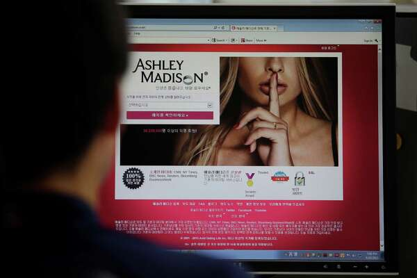 This file photo shows Ashley Madison's Korean web site on a computer screen in Seoul, South Korea. Ashley Madison — with its trademark manicured finger covering a foxy mouth — has been denounced, defended and, most grievously, taken seriously.