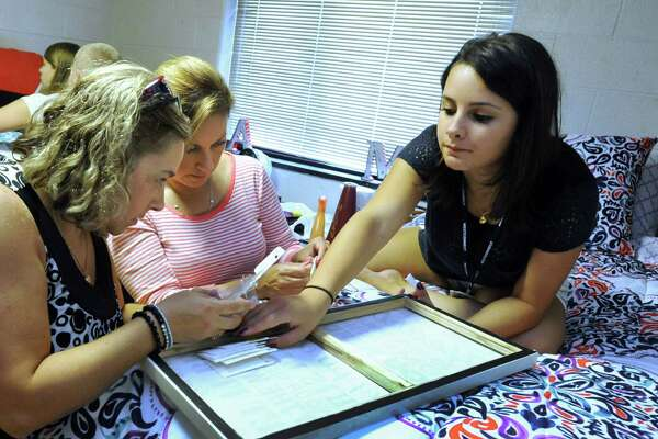 Megan Valentine, 17, right, gets help decorating her dorm room from mom Andrea Valentine, left, and aunt Rosana Walshaw, Friday, August 28, 2015. Friday was move-in day for freshmen at Western Connecticut State University.