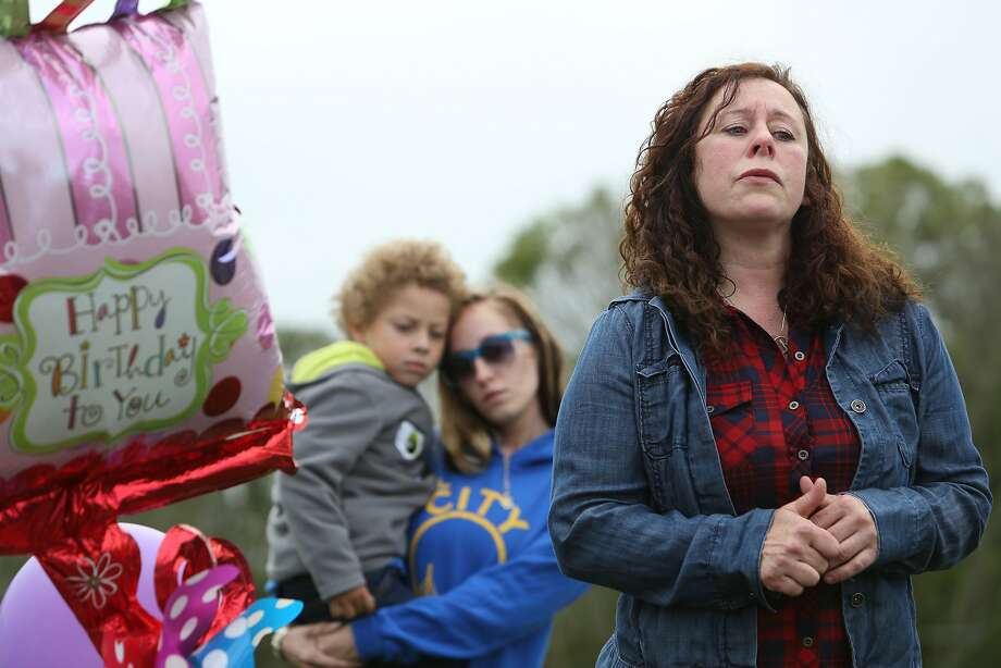 Rene Lynne Morales (right) talks to a gathering of family and friends at Woodlawn Cemetery to celebrate what would have been her daughter Jessica Lynne Morales' 25th birthday as her cousin Carissa Lynne Duran (center) holds her son Cassius Clay Duran Ward (left) in Colma. Jessica Lynne Morales was killed in the San Bruno gas pipeline explosion on Sept. 9, 2010. Photo: Lea Suzuki, The Chronicle