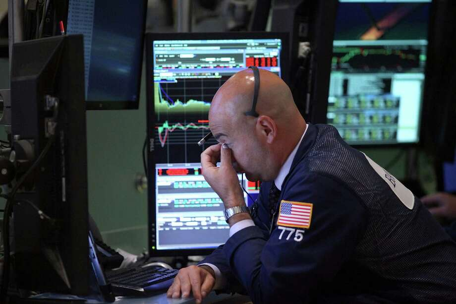 Traders work on the floor of the New York Stock Exchange on Tuesday, as the Dow Jones industrial average resumed its fall over uncertainty in the Chinese economy and a looming decision over interest rate hikes. It closed down nearly 470 points. Photo: Spencer Platt /Getty Images / 2015 Getty Images