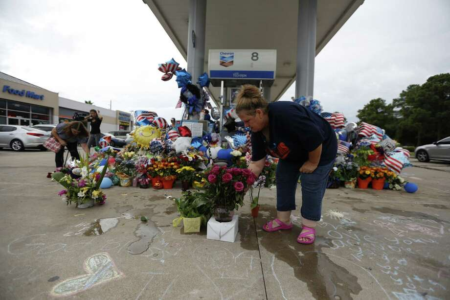Jennifer Spoonts moves flowers infront of a large memorial for slain Deputy Darren Goforth continues to grow Tuesday, Sept. 1, 2015, in Houston. Goforth was shot while returning to his patrol car Friday at a Chevron gas station. He was shot multiple times in the back and then shot multiple times once he was on the ground. ( Steve Gonzales / Houston Chronicle ) Photo: Steve Gonzales, Staff / © 2015 Houston Chronicle