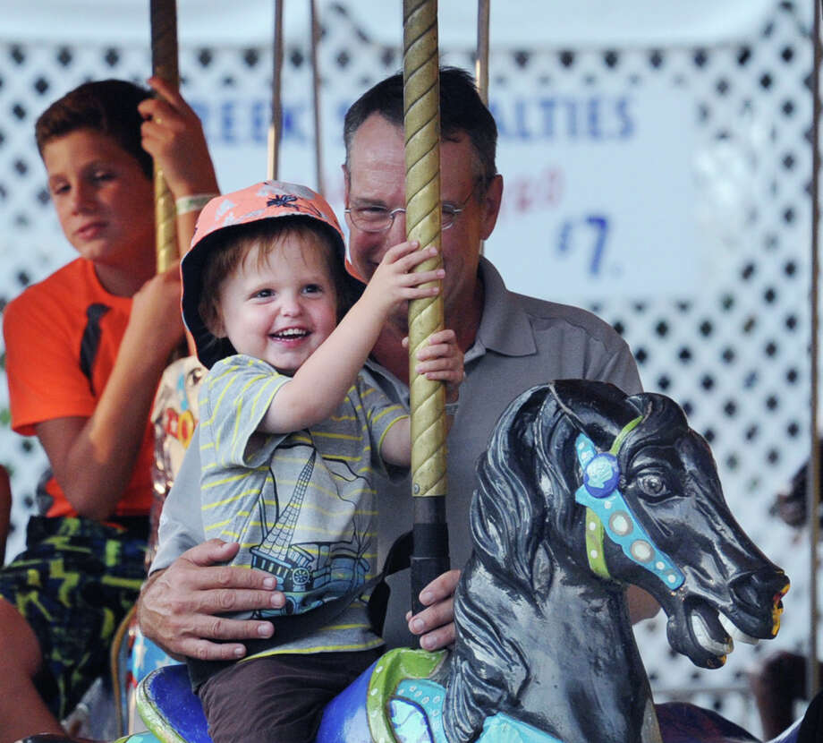 Zachary Price, 3, clutches onto a pole while riding a carousel pony as he is held by his father, Daivd Price, during the  annual St. Leo Fair at St. Leo Parish in Stamford, Conn., Tuesday night, Sept. 1, 2015. Photo: Bob Luckey Jr. / Hearst Connecticut Media / Greenwich Time