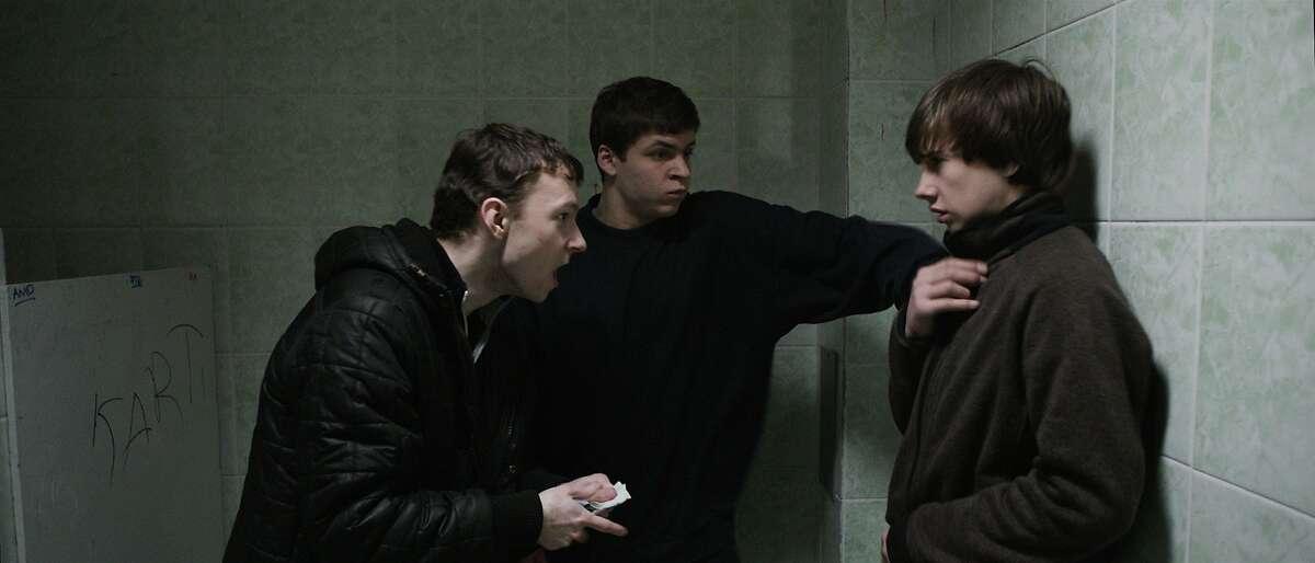 "Shnyr (Alexandr Sidelnikov), left, and Sergey (Grigoriy Fesenko), center, threaten a younger schoolmate in ""The Tribe."" Courtesy of Drafthouse Films"