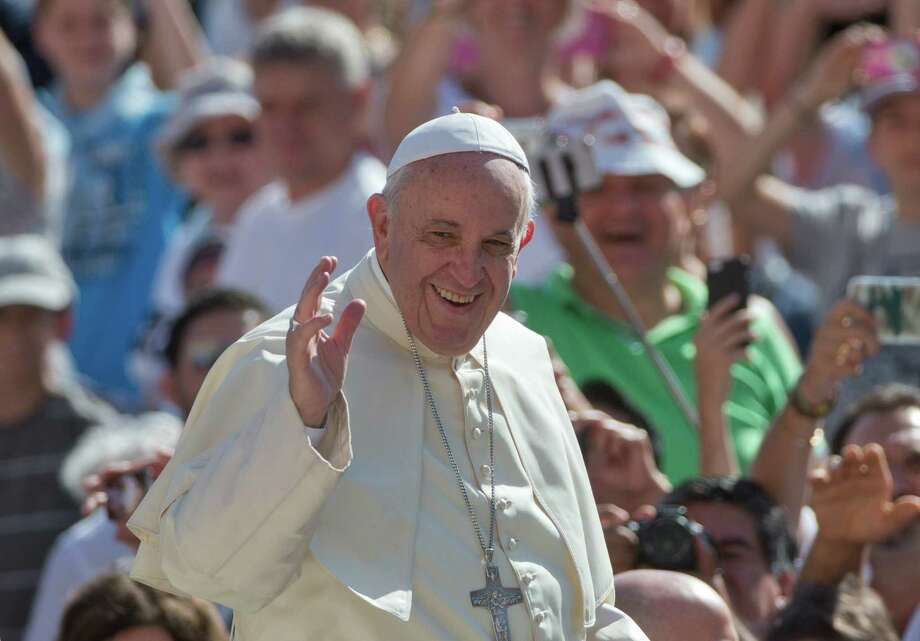 Pope Francis waves as arrives for his weekly general audience in St. Peter's Square at the Vatican on Wednesday. The pope spoke via satellite Monday with people in McAllen, Chicago and Los Angeles as he prepares to visit the United States later this month. Photo: Alessandra Tarantino /Associated Press / AP