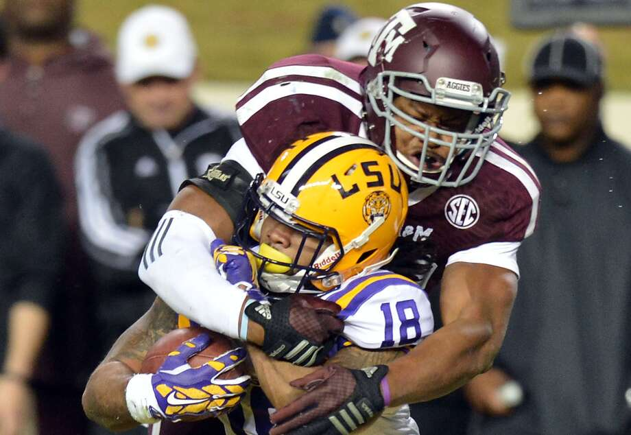 Texas A&M linebacker Shaan Washington tackles LSU running back Terrence Magee (18) for a loss on third down during the third quarter of an NCAA college football game Thursday, Nov. 27, 2014, in College Station, Texas. LSU won 23-17. Photo: Sam Craft /Associated Press / The Bryan-College Station Eagle