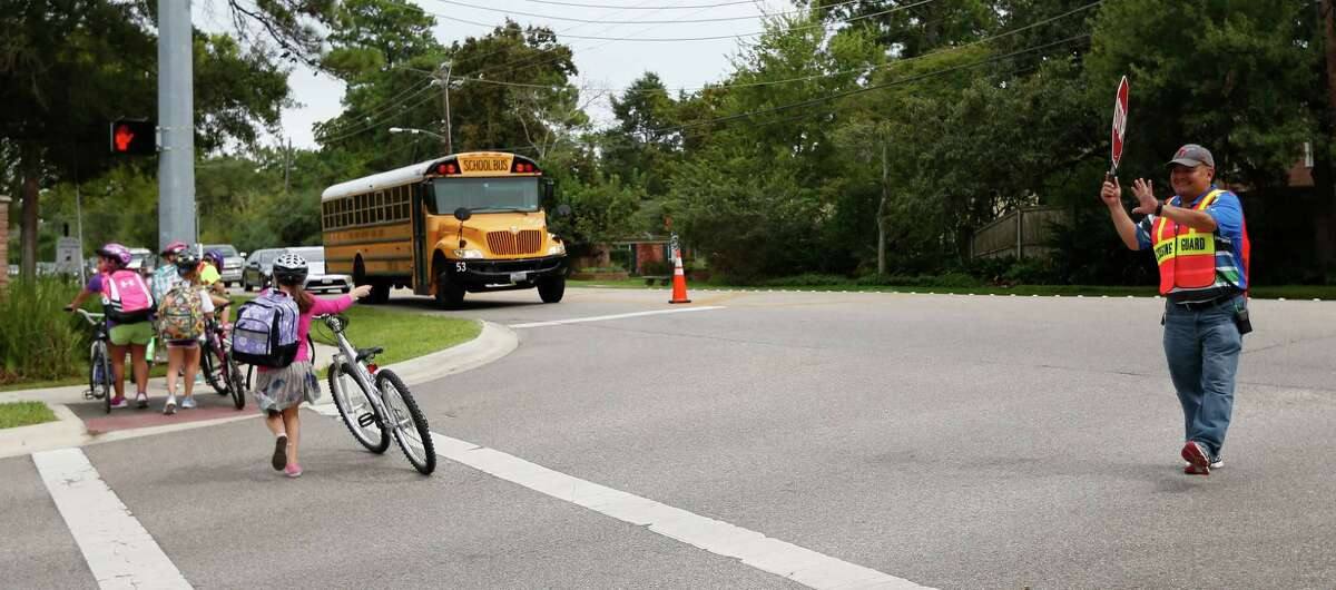 Jesus Ochoa helps children from Frostwood Elementary School cross on Memorial Drive as they walk home from school on Tuesday, Sept. 1, 2015. A 2009 state law banning cell phones in school zones. Law requires signs posted.