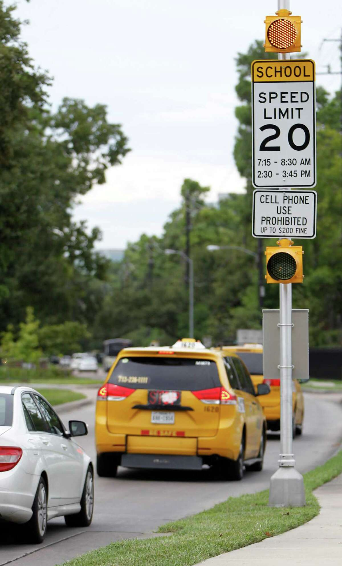 """Traffic passes a """"cell phone prohibited"""" sign on Gessner in front of Frostwood Elementary School on Tuesday, Sept. 1, 2015.A 2009 state law prohibits texting and hand-held cell phone use in school zones, but cities must post signs to enforce the ban."""