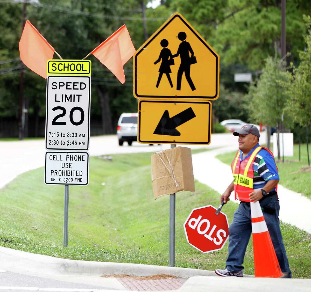 Jesus Ochoa helps children from Frostwood Elementary School cross on Memorial Drive as they walk home from school on Tuesday, Sept. 1, 2015.A 2009 state law prohibits texting and hand-held cell phone use in school zones, but cities must post signs to enforce the ban.