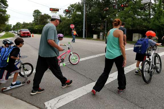 Jesus Ochoa helps parent and their children from Frostwood Elementary School cross on Memorial Drive as they walk home from school on Tuesday, Sept. 1, 2015. A 2009 state law banning cell phones in school zones. Law requires signs posted.