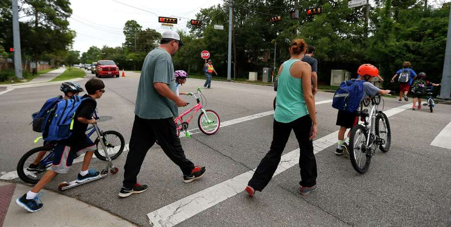 Jesus Ochoa helps parents and their children from Frostwood Elementary School cross on Memorial Drive as they walk home from school on Tuesday, Sept. 1, 2015. Photo: Karen Warren, Houston Chronicle / © 2015 Houston Chronicle