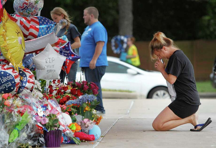 Dawn Crooks kneels in prayer at a memorial for Harris County Deputy Darren Goforth. Goforth was shot to death Sept. 1.   ( Steve Gonzales / Houston Chronicle ) Photo: Steve Gonzales, Staff / © 2015 Houston Chronicle