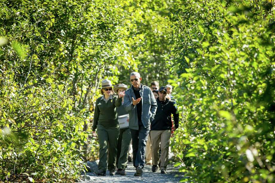 President Barack Obama speaks with a National Park Service employee as he take a hike to view the Exit Glacier in Seward, Alaska, Tuesday, Sept. 1, 2015, which according to National Park Service research, has retreated approximately 1.25 miles over the past 200 years. Obama is on a historic three-day trip to Alaska aimed at showing solidarity with a state often overlooked by Washington, while using its glorious but changing landscape as an urgent call to action on climate change. (AP Photo/Andrew Harnik) ORG XMIT: AKAH118 Photo: Andrew Harnik / AP