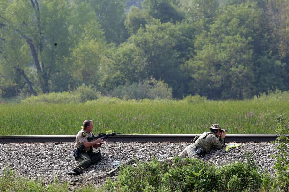 Police officers patrol a swampy area in Fox Lake, Ill., during a manhunt after an officer was shot and killed while pursuing a group of suspicious men, Tuesday, Sept. 1, 2015. Authorities in Fox Lake, 55 miles north of Chicago,  have notified a number of other law enforcement agencies to ask for assistance, including the FBI, which is sending agents to help in the investigation. (Stacey Wescott/Chicago Tribune via AP) MANDATORY CREDIT CHICAGO TRIBUNE; CHICAGO SUN-TIMES OUT; DAILY HERALD OUT; NORTHWEST HERALD OUT; THE HERALD-NEWS OUT; DAILY CHRONICLE OUT; THE TIMES OF NORTHWEST INDIANA OUT; TV OUT; MAGS OUT; NO SALES    ORG XMIT: ILCHT103 Photo: Stacey Wescott / Chicago Tribune
