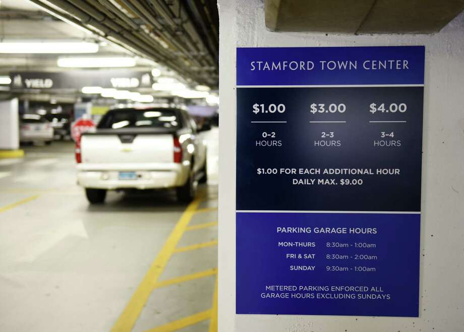 A new parking rates sign hangs inside the Stamford Town Center parking garage. This week, the mall replaced its metered parking with an electronic pay station system, boosting the hourly rate. he old metered parking rates were 50 cents for two hours and 75 cents for fours hours, but the new electronic system is $1 for two hours, $3 for three hours and $4 for four hours. Photo: Tyler Sizemore / Hearst Connecticut Media / Greenwich Time