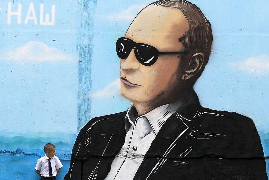 A boy stands by a wall sprayed with a graffiti depicting Russia's President Vladimir Putin in the Crimean city of Simferopol on September 1, 2015. Photo: Yuri Lashov, AFP / Getty Images