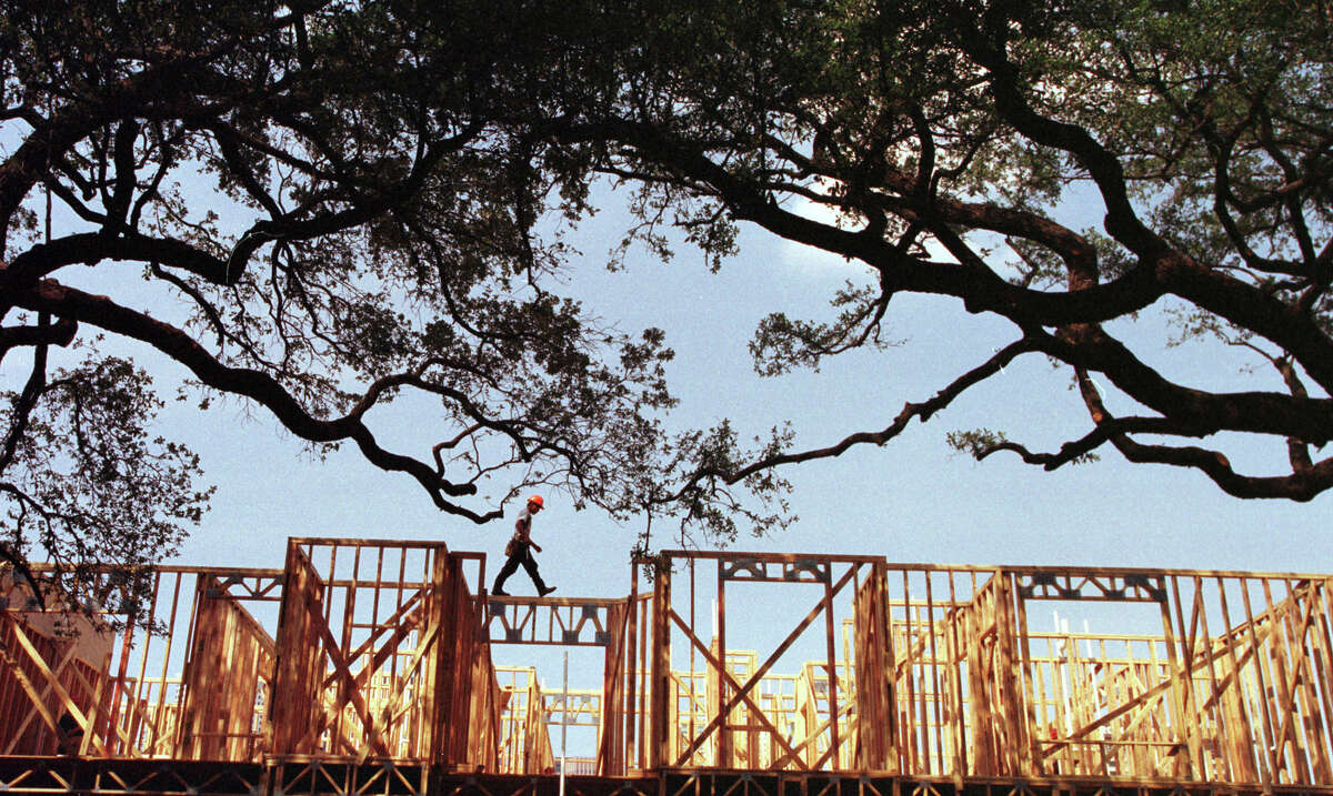 CONTACT FILED: APARTMENTS-HOUSTON HOUSTON PROJECT 2000. Houstonians at work. 'Woodscapes'...a carpenter (no I.D.) walks along the framing of new apartment construction amidst the trees in the booming Midtown area. This photo taken in August, 1998. HOUCHRON CAPTION (01/02/2000): As if casually strolling down a country lane, a construction worker walks atop the framing of an apartment building going up in the booming Midtown area. HOUSTON CHRONICLE SPECIAL SECTION/TEXAS MAGAZINE: HOUSTON AT 2000.