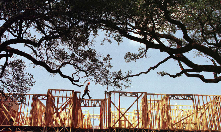 CONTACT FILED:  APARTMENTS-HOUSTON HOUSTON PROJECT 2000.  Houstonians at work. 'Woodscapes'...a carpenter (no I.D.) walks along the framing of new apartment construction amidst the trees in the booming Midtown area.    This photo taken in August, 1998.  HOUCHRON CAPTION (01/02/2000): As if casually strolling down a country lane, a construction worker walks atop the framing of an apartment building going up in the booming Midtown area.  HOUSTON CHRONICLE SPECIAL SECTION/TEXAS MAGAZINE: HOUSTON AT 2000. Photo: John Everett, Staff / Houston Chronicle
