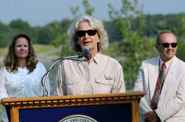 Carol Clement, an owner of Heather Ridge Farm, center, talks about the City's Water Board employing goats during a news conference on Wednesday, Sept. 2, 2015, at the Loudonville Reservoir in Albany , N.Y. Joining her are Amy Walsh, forester of the Water Board, left, and Commissioner Joseph Coffey of the Water Board. The goats, owned by Heather Ridge Farm, will chew away nearly three acres of overgrowth along a steep slope. (Cindy Schultz / Times Union) Photo: Cindy Schultz / 00033209A