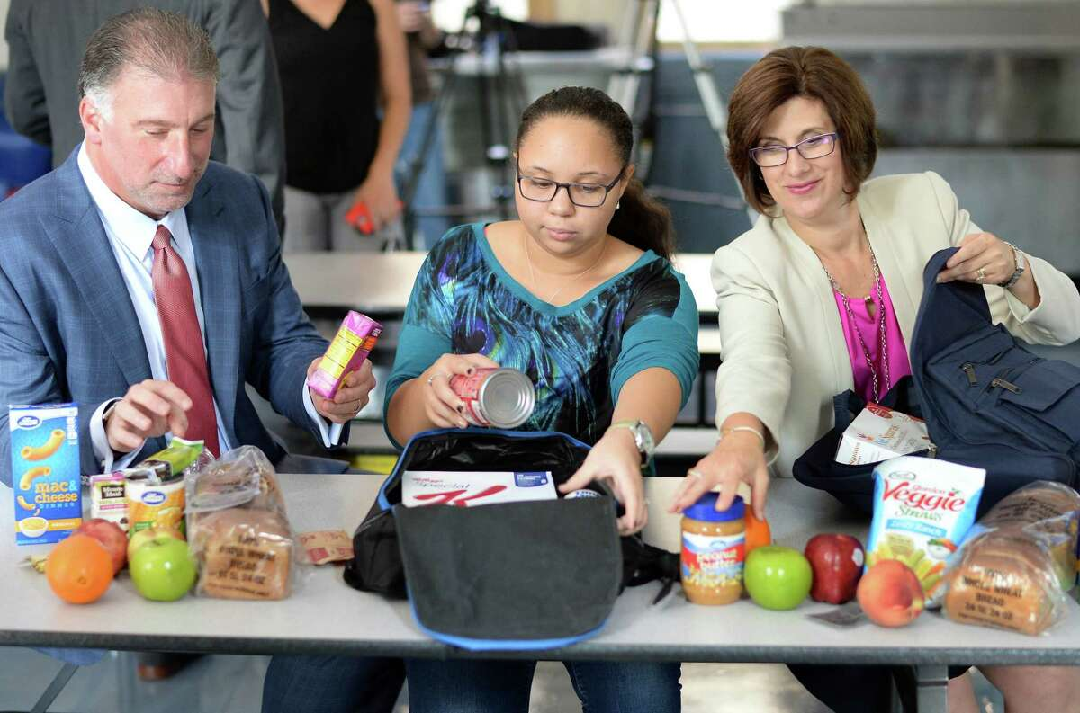 SEFCU President and CEO Michael J. Castellana, left, student volunteer, Paige 7th grader Myasya Mayotte and MVP Health Care President and CEO Denise Gonick, right, pack bags for the Weekend Backpack Partnership Wednesday Sept. 2, 2015 at Pleasant Valley School in Schenectady, NY. (John Carl D'Annibale / Times Union)