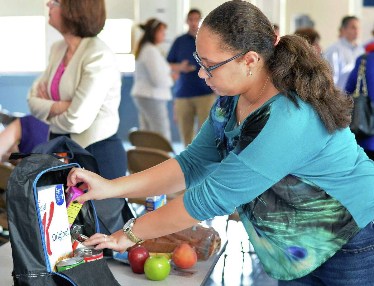 Paige 7th grader Myasya Mayotte packs bags for the Weekend Backpack Partnership Wednesday Sept. 2, 2015 at Pleasant Valley School in Schenectady, NY. (John Carl D'Annibale / Times Union)