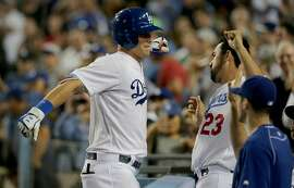 The Los Angeles Dodgers' Joc Pederson, left, is congratulated by teammate Adrian Gonzalez after hitting a solo home run against the San Francisco Giants in the seventh inning at Dodger Stadium in Los Angeles on Tuesday, Sept. 1, 2015. The Dodgers won, 2-1. (Luis Sinco/Los Angeles Times/TNS)