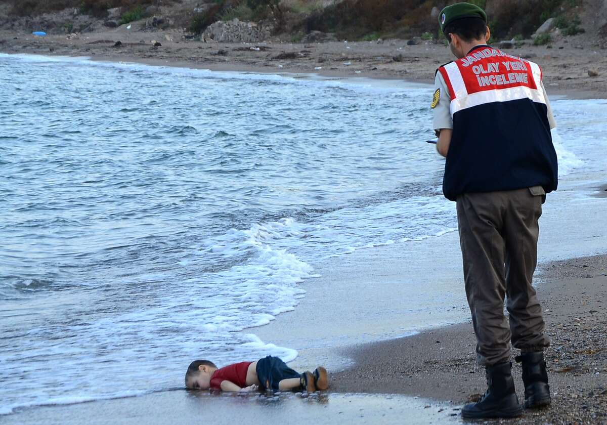 A Turkish police officer stands next to a migrant child's dead body off the shores in Bodrum, southern Turkey, on Sept. 2, after a boat carrying refugees sank while reaching the Greek island of Kos.