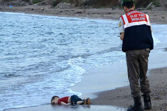 A Turkish police officer stands next to a migrant child's dead body off the shores in Bodrum, southern Turkey, on September 2, 2015 after a boat carrying refugees sank while reaching the Greek island of Kos. Thousands of refugees and migrants arrived in Athens on September 2, as Greek ministers held talks on the crisis, with Europe struggling to cope with the huge influx fleeing war and repression in the Middle East and Africa. AFP PHOTO / DOGAN NEWS AGENCY = TURKEY OUT =STR/AFP/Getty Images