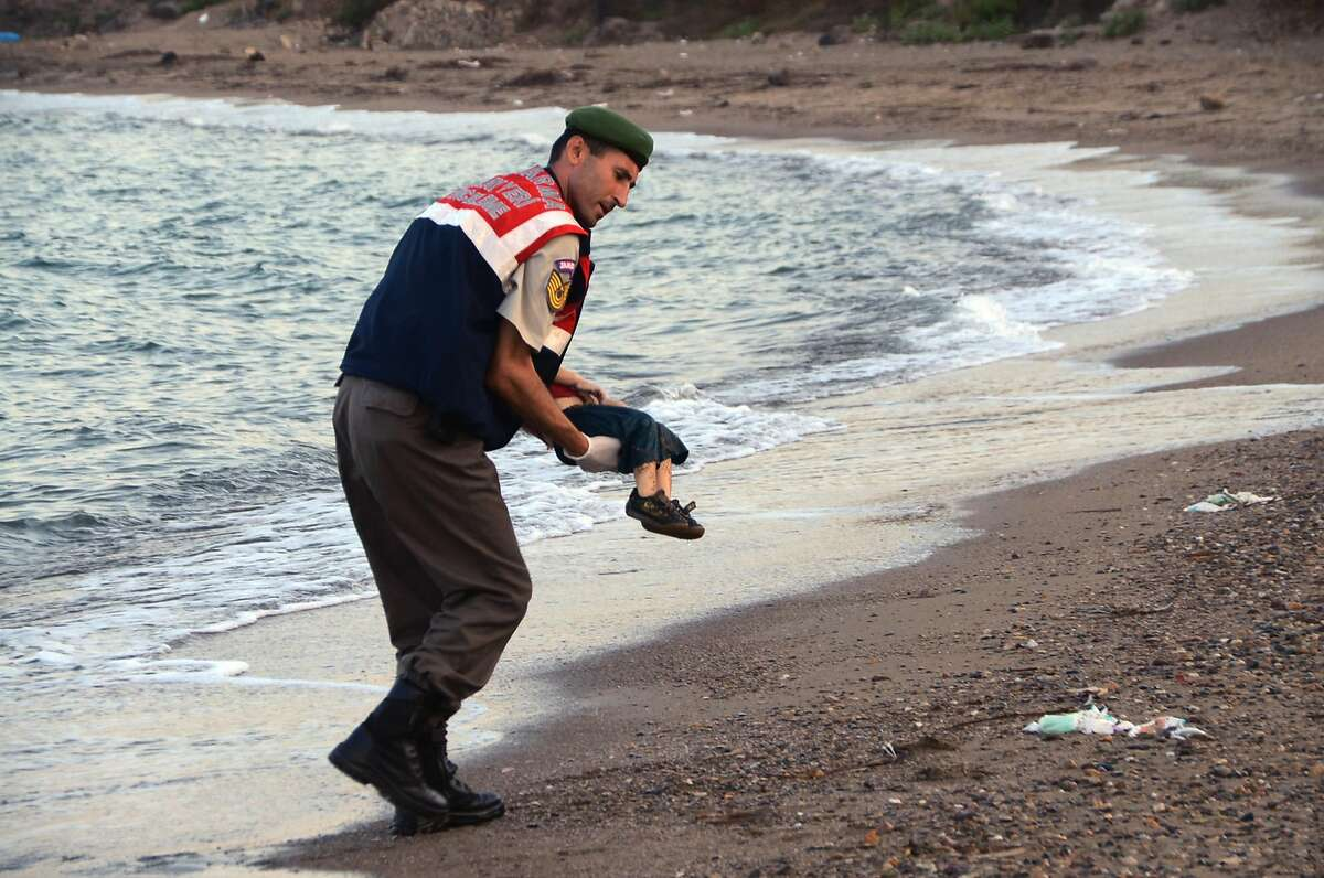 A Turkish police officer carries a migrant child's body off the shores in Bodrum, southern Turkey, after a boat carrying refugees sank Tuesday while attempting to reach the Greek island of Kos.