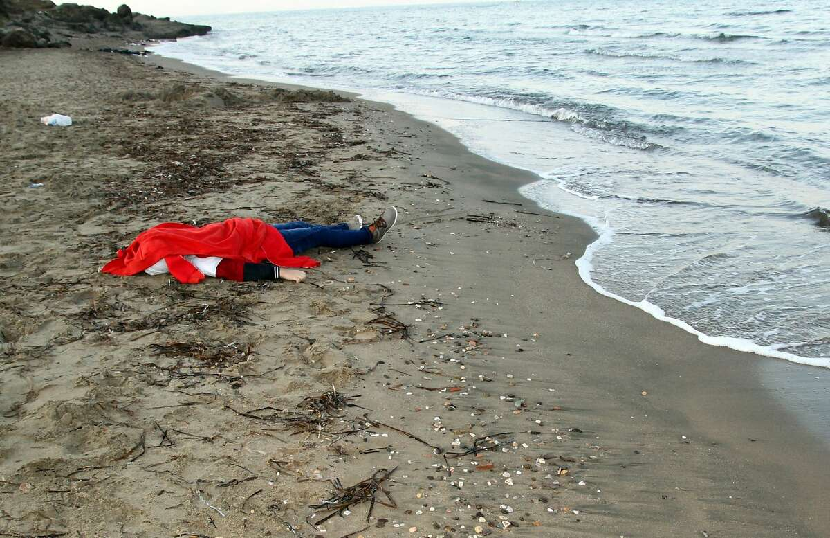 The body of one of two young brothers who drowned when a boat carrying migrants capsized Tuesday lies on a beach in Bodrum, Turkey.