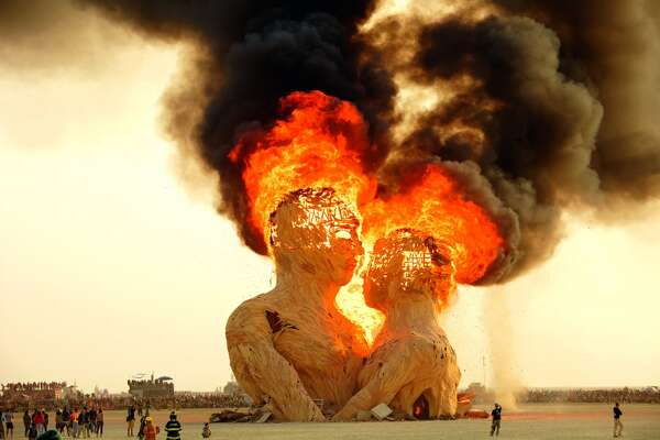 Embrace, 2014. Artists: Kevan Christiaens, Kelsey Owens, Bill Tubman, Joe Olivier, Matt Schultz and the Pier Group. Embrace, a 70-foot-tall wooden sculpture, burns at dawn. The work symbolizes the nature of human relationship and was built to burn.