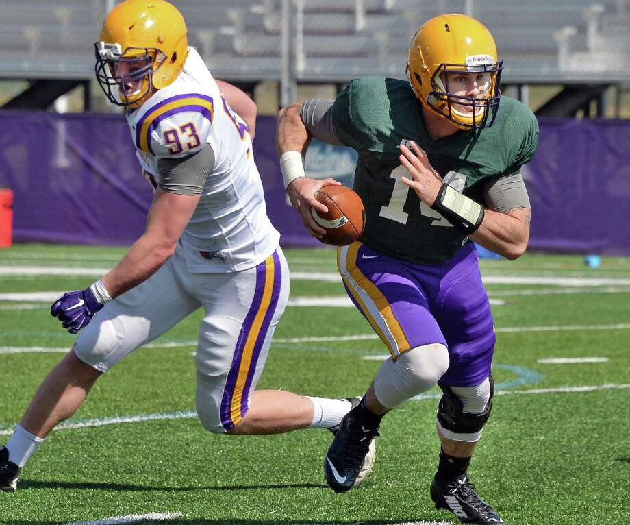 Quarterback #14 DJ Crook, right, scrambles past #93 Jack Forster during UAlbany football's Spring Game Saturday April 18, 2015 in Albany, NY.  (John Carl D'Annibale / Times Union) Photo: John Carl D'Annibale / 00031485A