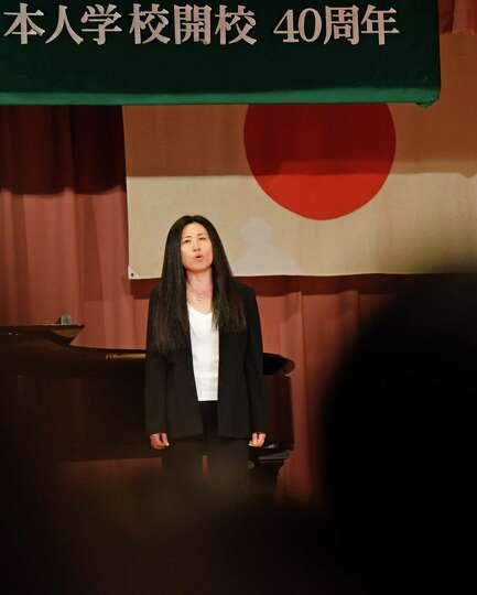 Junior high music teacher Yuki Otska sings during the 40th anniversary assembly at the Japanese Scho
