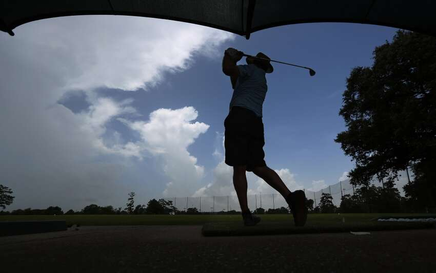Round of golf Kirk Girouard swings to hit a golf ball at the Memorial Park driving range on Monday, June 29, 2015, in Houston. Scoring a Sunday morning tee-time at this well-known Houston golf course can cost about $60, including greens fees and cart rental. ( Mayra Beltran / Houston Chronicle )