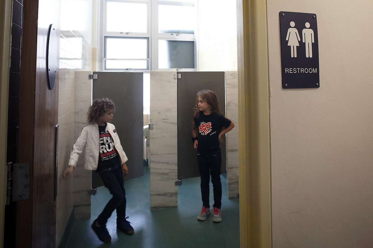 First grade twins Ari Braverman (left), and Ella Braverman (right), both 6 years old, show first grade gender neutral bathrooms at Miraloma Elementary school in San Francisco, Calif., on Wednesday, September 2, 2015.