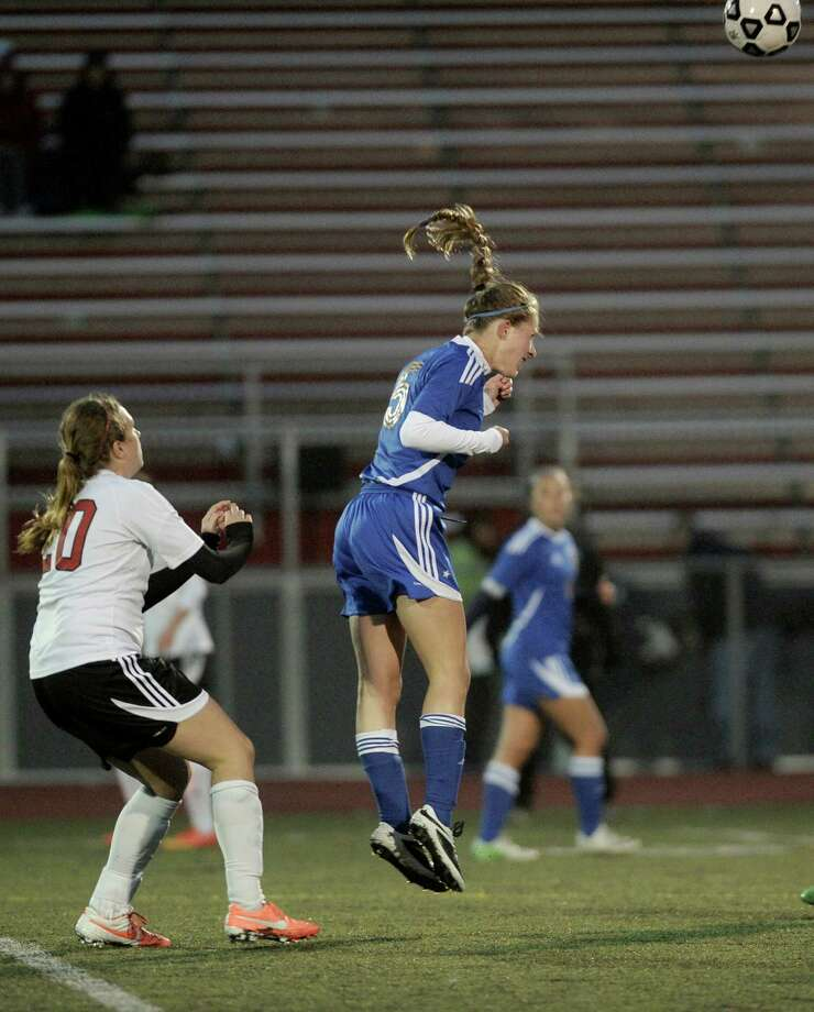 Newtown's Madeline Sieber (5) heads the ball away from Pomperaug's Justine Troiano (20) during the high school girls soccer game between Newtown and Pomperaug, on Wednesday, October 22, 2014, in Southbury, Conn. Photo: H John Voorhees III / H John Voorhees III / The News-Times Staff Photographer