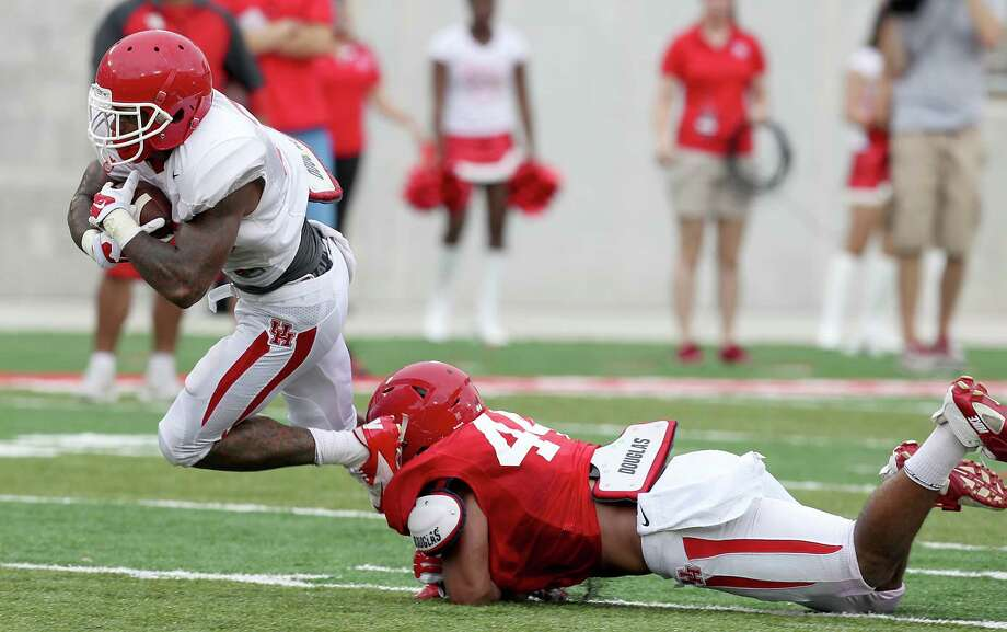 White team running back Javin Webb (28) is tackled by Red team inside linebacker Elandon Roberts (44) in the Spring Red and White game on April 18, 2015 at TDECU Stadium in Houston, TX. White won 24 to 11. (Photo: Thomas B. Shea/For the Chronicle) Photo: Thomas B. Shea, Freelance / © 2015 Thomas B. Shea