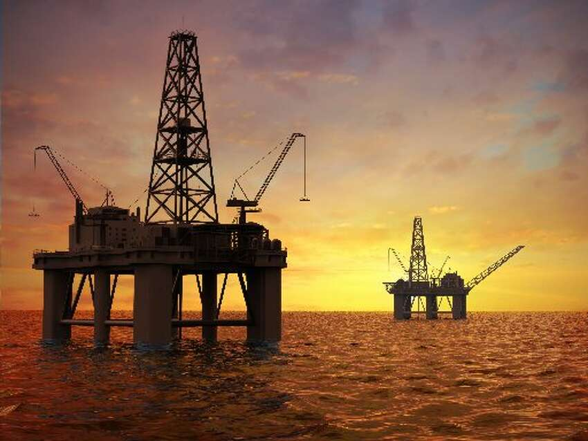Offshore oil derricks stand in silhouette against an ocean sky. (Getty images)