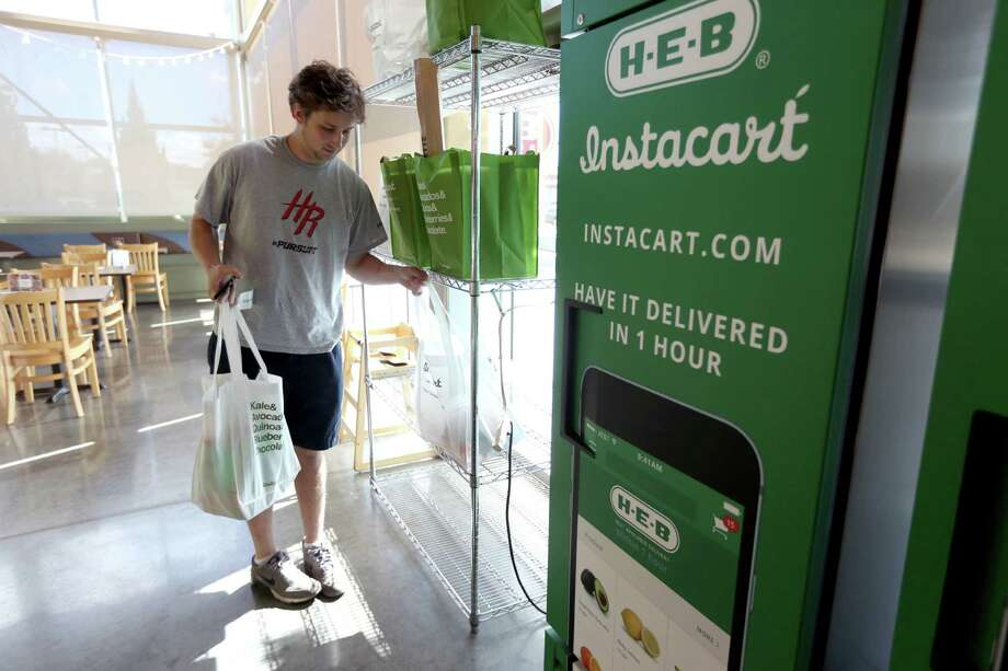 Douglas Gates, an Instacart employee, gathers items from an Instacart staging area at an H-E-B to be delivered to a home.  Photo: Gary Coronado, Staff / © 2015 Houston Chronicle