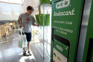 Douglas Gates, an Instacart employee, gathers items from an Instacart staging area at an H-E-B to be delivered to a home.