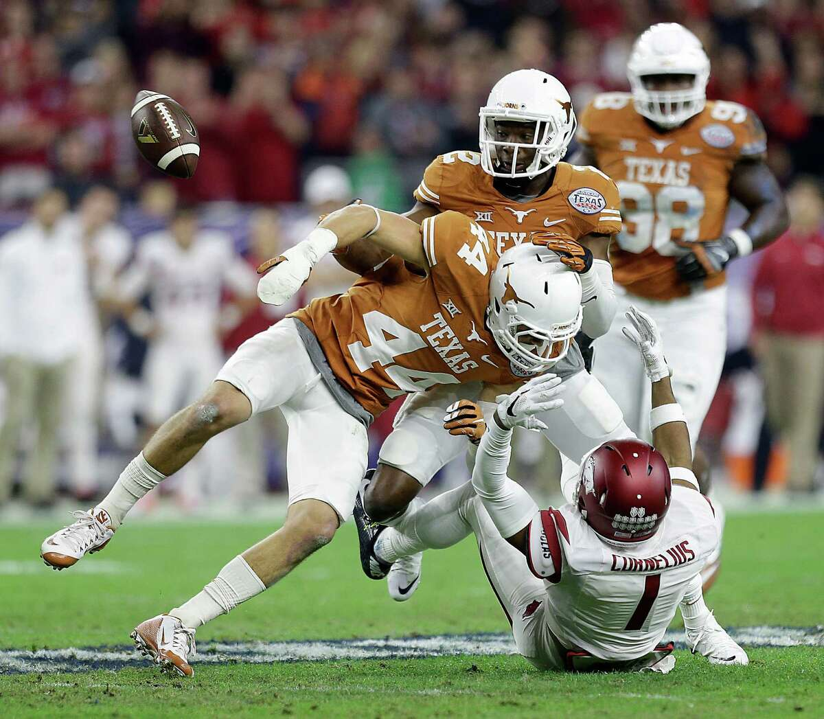 Arkansas wide receiver Jared Cornelius (1) loses control of the ball as he was tackled by Texas defensive back Dylan Haines (44) and safety Mykkele Thompson (2) during the first quarter of the Texas Bowl at NRG Stadium on Dec. 29, 2014, in Houston.