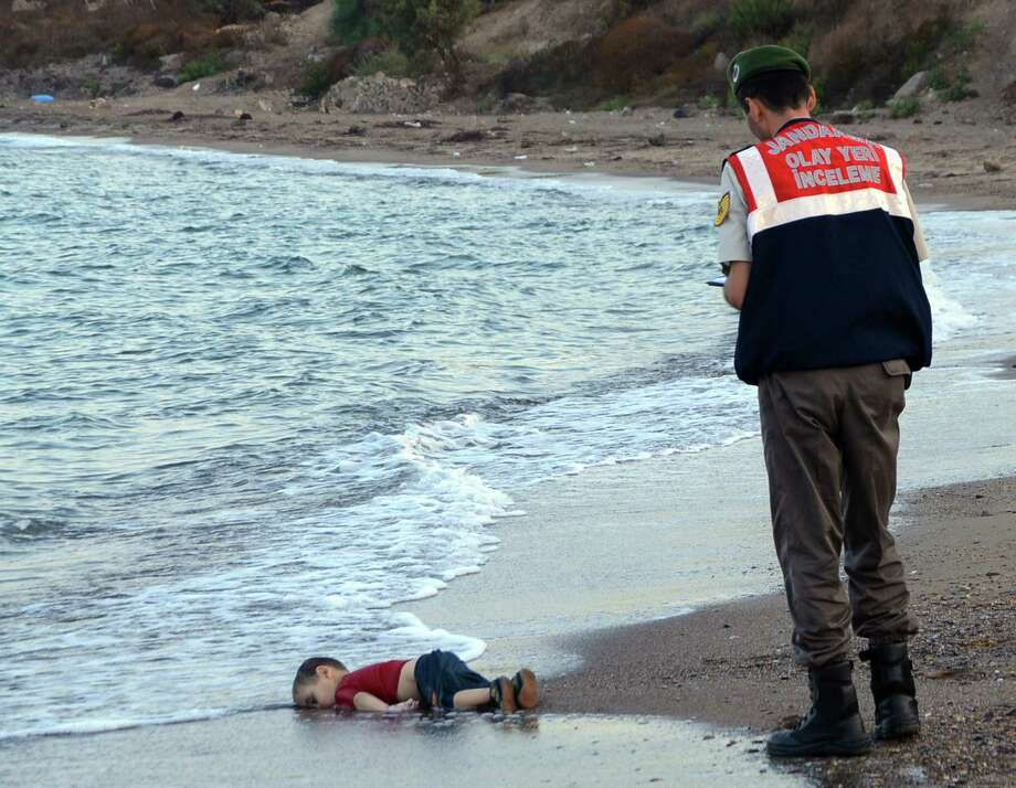 Paramilitary police officers investigate the scene before carrying the lifeless body of an unidentified migrant child, lifting it from the sea shore, near the Turkish resort of Bodrum, Turkey, early Wednesday, Sept. 2, 2015. A number of migrants are known to have died and some are still reported missing, after boats carrying them to the Greek island of Kos capsized. (AP Photo/DHA) TURKEY OUT - ONLINE OUT Photo: Uncredited, SUB / DHA