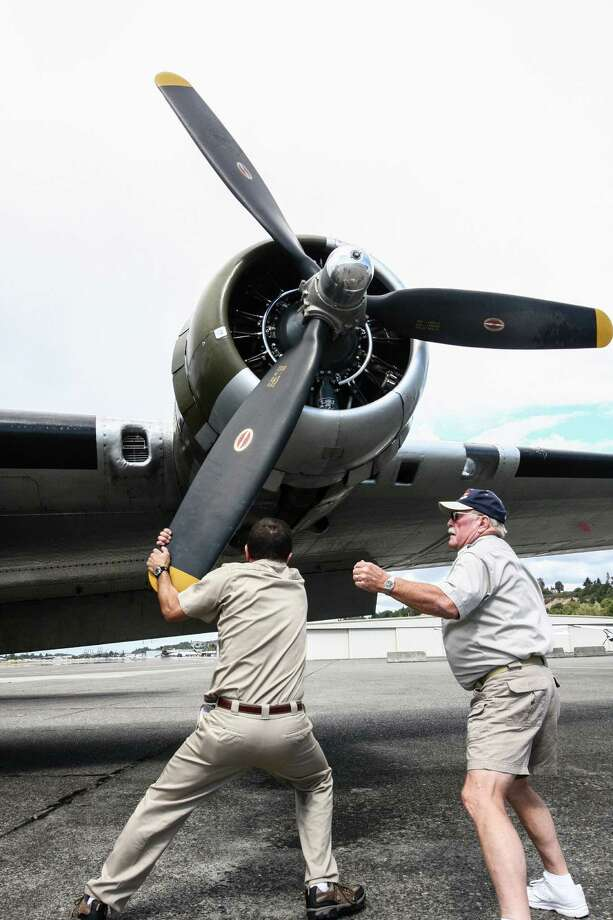 Crew Chief Richard Taracka and a Cascade Warbirds tour host spin one of the propellers of Aluminum Overcast, a Boeing B-17 Flying Fortress, before a flight Wednesday, Sept. 2, 2015. The plane will be on display at the Museum of Flight and conducting passenger flights Friday through Monday. Photo: DANIEL DEMAY/SEATTLEPI.COM