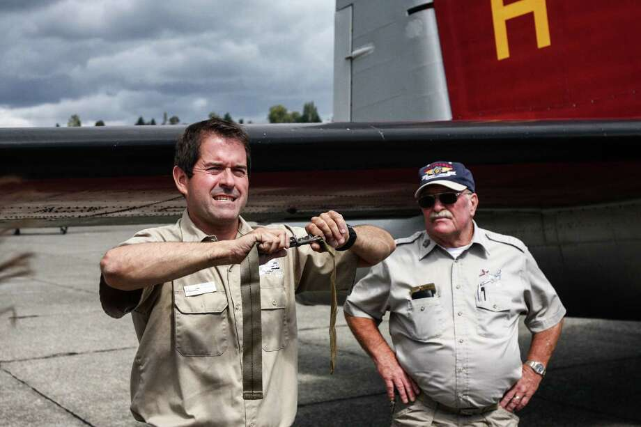 """Crew Chief Richard Taracka demonstrates the """"military style"""" seat belt of the Boeing B-17 Flying Fortress Wednesday, Sept. 2, 2015, before a flight aboard Aluminum Overcast, as the plane is called. The plane will be on display at the Museum of Flight and conducting passenger flights Friday through Monday. Photo: DANIEL DEMAY/SEATTLEPI.COM"""