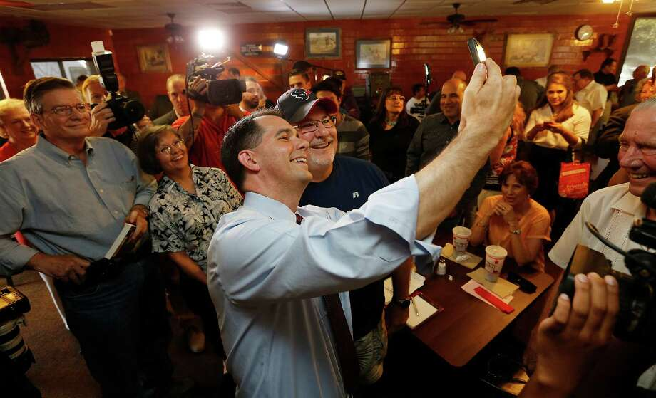 Republican presidential candidate Scott Walker (center) poses for a photo with Garden Ridge resident Dexter Cochnauer during a campaign stop in San Antonio at a Bill Miller's Restaurant off Broadway on Wednesday, Sept. 2, 2015. Walker was greeted by supporters and media after he made an earlier stop in Dallas for his bid to become the GOP candidate. (Kin Man Hui/San Antonio Express-News) Photo: Kin Man Hui, Staff / San Antonio Express-News / ©2015 San Antonio Express-News