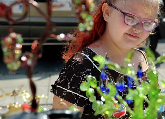 Kennedy Reed, 7, of Selkirk looks over the the glass art at the Castle Green Art Glass booth during September in the City Art Fair on Wednesday, Sept. 2, 2015, at Tricentennial Park in Albany , N.Y. The event series features art, music and culture every Wednesday in September from 11:30 a.m. to 2 p.m. (Cindy Schultz / Times Union) Photo: Cindy Schultz / 00033186A