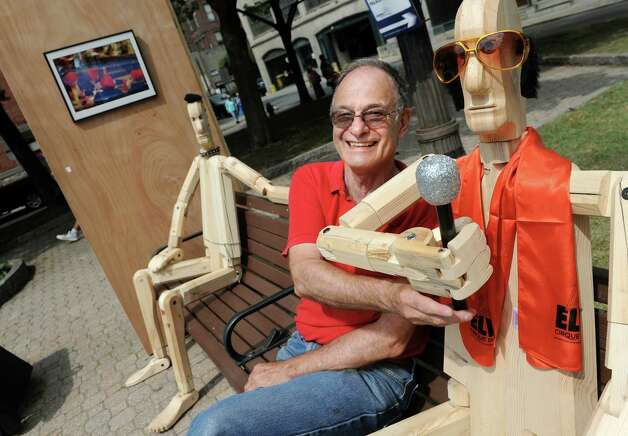 "Artist Peter Leue of Albany adjusts the microphone of ""Elvis,"" one of Leue's life-sized, wooden Posers, during September in the City Art Fair on Wednesday, Sept. 2, 2015, at Tricentennial Park in Albany , N.Y. The event series features art, music and culture every Wednesday in September from 11:30 a.m. to 2 p.m. (Cindy Schultz / Times Union) Photo: Cindy Schultz / 00033186A"