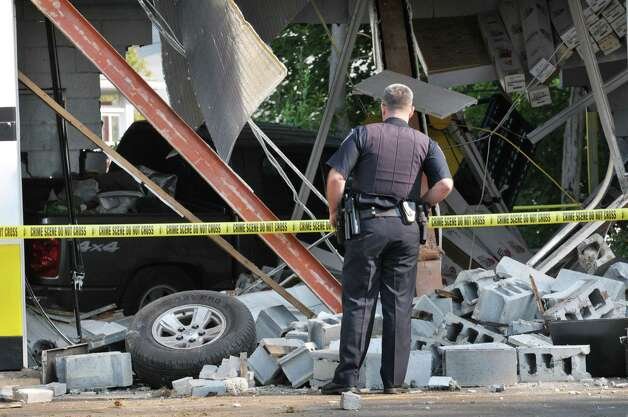 A Colonie Police officer surveys damage to the Tint King garage on Central Avenue Wednesday morning, Sept. 2, 2015, after a pickup truck left the road late Tuesday, took out a utility pole and slammed into the building in Colonie, N.Y. (Will Waldron/Times Union) Photo: Will Waldron / 00033215A