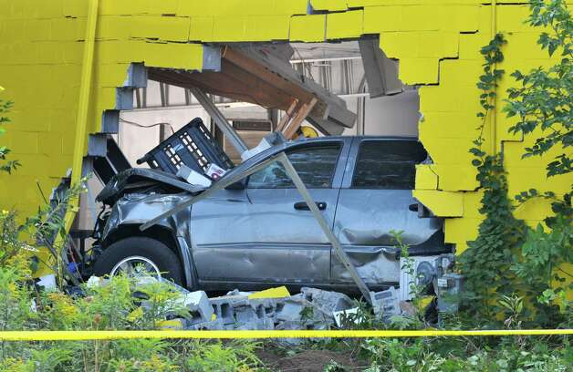 A pickup truck rests in the Tint King garage on Central Avenue Wednesday morning, Sept. 2, 2015, after it left the road late Tuesday, took out a utility pole and slammed into the building in Colonie, N.Y. (Will Waldron/Times Union) Photo: Will Waldron / 00033215A