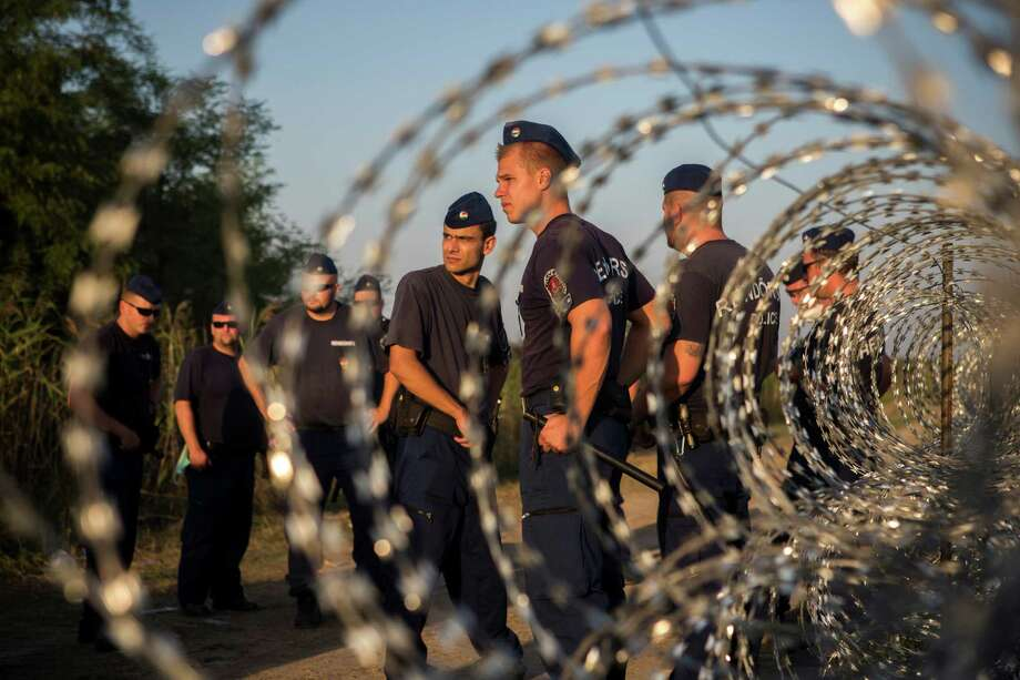 Hungarian policemen stand guard near to the Hungarian town of Roszke at the border with Serbia, on Wednesday Sept. 2, 2015. The 28-nation European Union has been at odds for months on how to deal with the influx of more than 332,000 migrants this year as Greece, Italy and Hungary have pleaded for more help. (AP Photo/Santi Palacios) ORG XMIT: XTS114 Photo: Santi Palacios / AP
